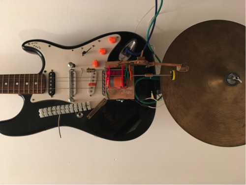 Picture of a modified guitar with a cymbal attached and wires