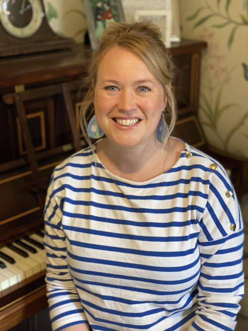 A white woman with blond hair smiles at the camera. She is in front of a piano.